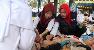 Dua orang tim medis PMI Blora memberikan pertolongan pertama kepada siswa sekolah yang pingsan saat mengikuti upacara detik-detik kemerdekaan RI di Alun-Alun Blora.  (Foto: Humas PMI)