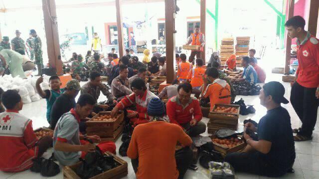 MEMBANTU : Relawan dari PMI Blora sedang membantu pengepakan di Posko Penanngulangan Bencana Kecamatan Gubug Kabupaten Grobogan yang terkena bencana banjir.  (Foto: dok Satgana)