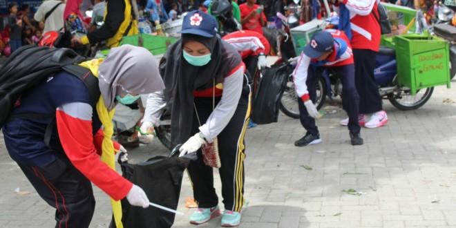 KUMPULKAN : Anggota PMI Blora sedang mengumpulkan sampah yang berserakan di jalan usai Kirab Hari Jadi Kabupaten Blora, Minggu (11/12). (PMI dok)